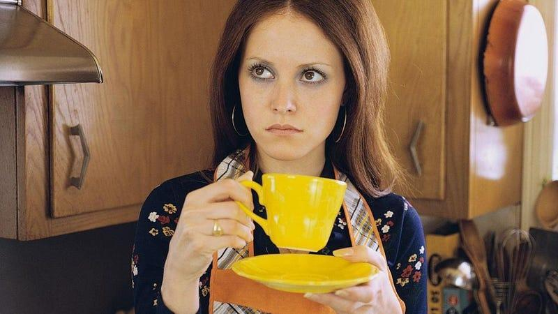 Woman staring off into distance while drinking out of yellow coffee mug