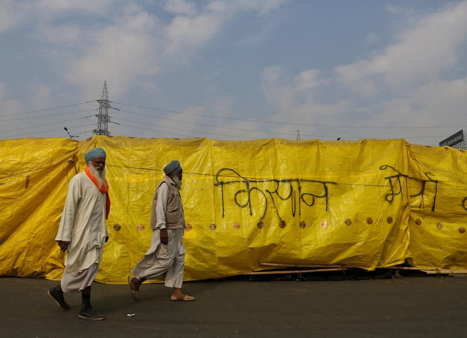 "NEW DELHI, INDIA - FEBRUARY 3:  Demonstrators walking past graffiti that reads ""Kisan Morcha"" at the Ghazipur border protest site on February 3, 2021 in New Delhi, India. The farmers protest at the Singhu, Tikri and Ghazipur borders against the farm laws entered the 68th day on Sunday. On Republic Day, farmer groups broke through barricades, clashed with the Delhi Police and stormed the Red Fort, hoisting the Nishan Sahib, the flag of the Sikhs, on its ramparts. An officer said that the security and barricading was tightened following the conflict between the farmers and local residents witnessed on Friday and Saturday over the issue of clearing the roads, and the violence at the Red Fort and other places in Delhi on January 26. (Photo by Sanchit Khanna/Hindustan Times via Getty Images)"