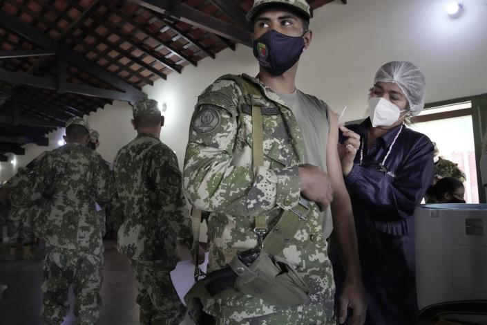 Sargent Ramon Florenciano receives a shot of the Pfizer COVID'19 vaccine from an Health Ministry worker at a military barracks in Mariano Roque Alonso, Paraguay, Monday, July 12, 2021. Essential workers like members of the armed forces, teachers, police have been authorized to be vaccinated in Paraguay. (AP Photo/Jorge Saenz)