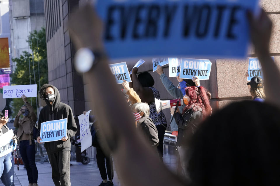 Demonstrators stand across the street from the federal courthouse in Houston, Monday, Nov. 2, 2020, before a hearing in federal court involving drive-thru ballots cast in Harris County. The lawsuit was brought by conservative Texas activists, who have railed against expanded voting access in Harris County, in an effort to invalidate nearly 127,000 votes in Houston because the ballots were cast at drive-thru polling centers established during the pandemic. (AP Photo/David J. Phillip)
