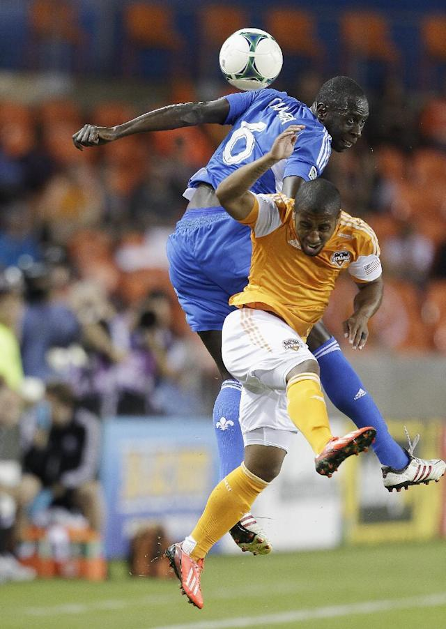 Houston Dynamo midfielder Corey Ashe (26) takes an elbow to the head from Montreal Impact defender Hassoun Camara (6) as they go up for a head ball in the first half during a knockout-round match in the MLS Cup soccer playoffs, Thursday, Oct. 31, 2013, in Houston. (AP Photo/Bob Levey)