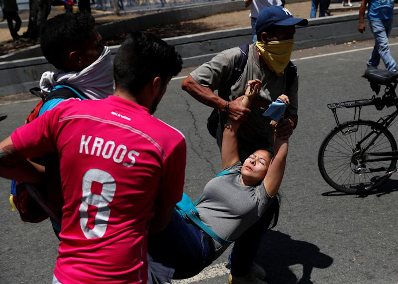 "Opposition demonstrators help an injured fellow near the Generalisimo Francisco de Miranda Airbase ""La Carlota"" in Caracas, Venezuela April 30, 2019. (Photo: Carlos Garcia Rawlins/Reuters)"