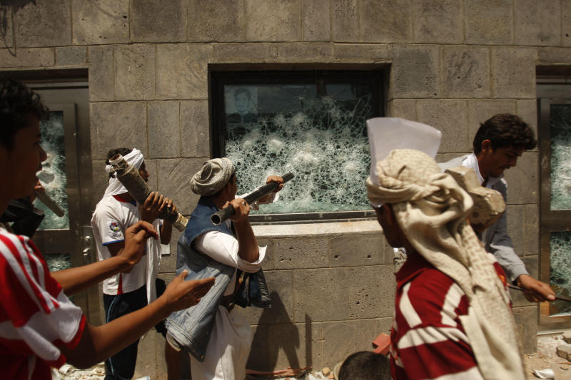 """Yemeni protesters break a window of the U.S. Embassy during a protest about a film ridiculing Islam's Prophet Muhammad, in Sanaa, Yemen, Thursday, Sept. 13, 2012. Dozens of protesters gather in front of the US Embassy in Sanaa to protest against the American film """"The Innocence of Muslims"""" deemed blasphemous and Islamophobic. (AP Photo/Hani Mohammed)"""