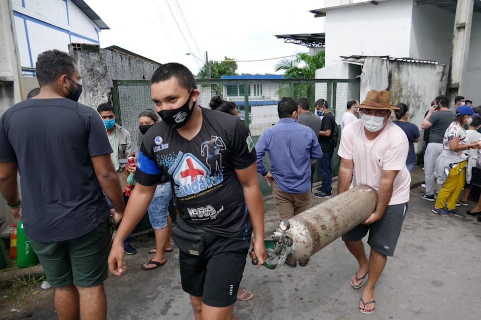 MANAUS , Jan. 15, 2021 -- Two people carry the oxygen cylinder at an oxygen factory in Manaus of Amazonas, Brazil, Jan. 15, 2021. Brazil's northern state of Amazonas moved to send 235 patients hospitalized for COVID-19 to other states as its healthcare system was stretched to the limit, Governor Wilson Lima said Thursday.    Hospitals in state capital Manaus are crowded and lack the oxygen needed to treat infected patients, he said. (Photo by Sandro Pereira/Xinhua via Getty) (Xinhua/Sandro Pereira via Getty Images)