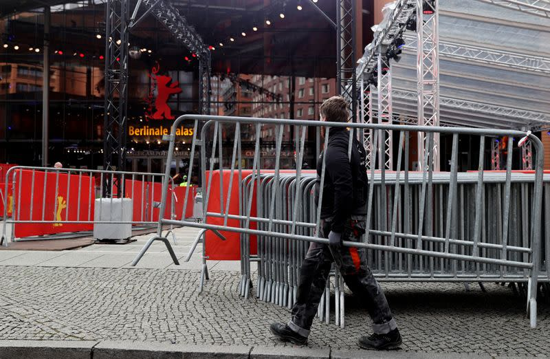 """A worker carries a barrier in front of the """"Berlinale Palast"""", where the competition movies will be screened at the upcoming 70th Berlinale International Film Festival in Berlin"""