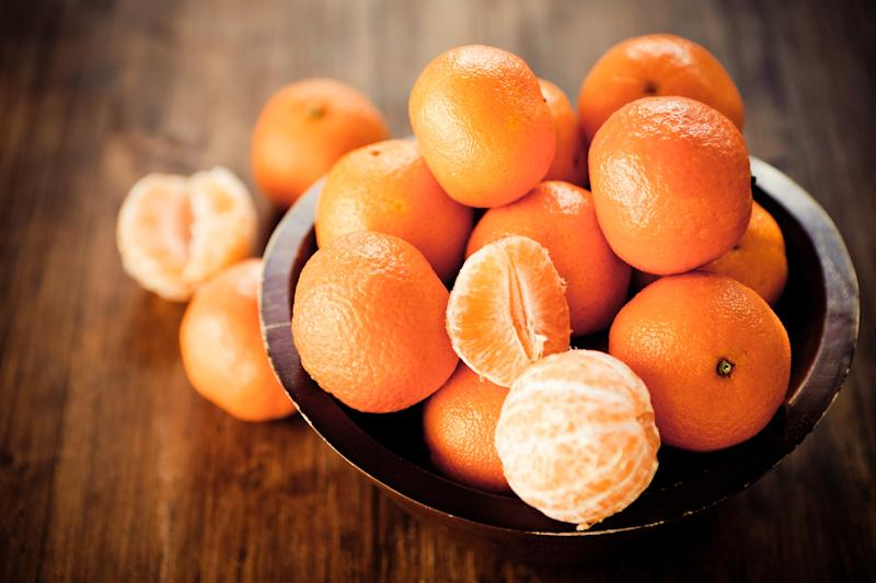 Citrus fruit: Clementines in a rustic wooden bowl.