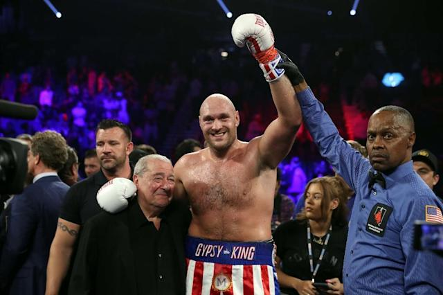 A victorious Tyson Fury has his arm raised by referee Kenny Bayless as he hugs veteran promoter Bob Arum after stopping Tom Schwarz in Las Vegas (AFP Photo/Steve Marcus)