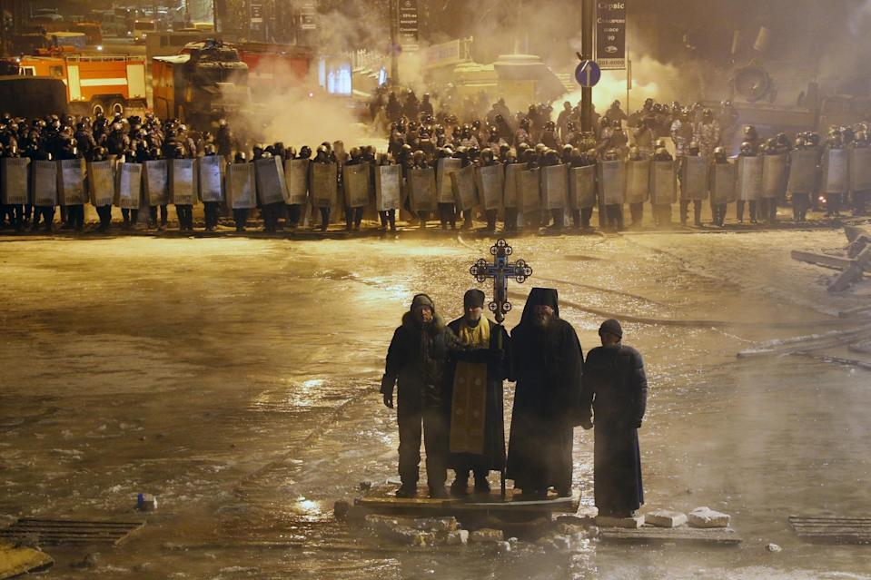FILE In this file photo taken on Friday, Jan. 24, 2014, Orthodox priests pray as they stand between pro-European Union activists and police lines in central Kiev, Ukraine. As a barricade of blazing tires belched thick black smoke, a line of priests stood between angry protesters and ominous riot police. Every freezing morning, priests sing prayers to demonstrators gathered on the Ukrainian capital's main square, a solemn and soothing interlude to vehement speeches calling for revolution. (AP Photo/Sergei Grits, file)