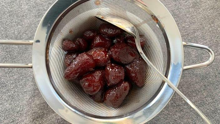 roasted strawberries in a strainer over a bowl