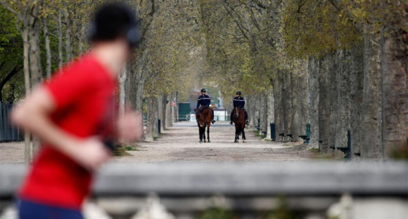 A Paris resident jogging during the lockdown while police on horseback watch