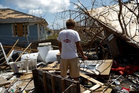 A man looks the devastated cabin at the back yard of his house after Hurricane Dorian hit the Abaco Islands in Spring City