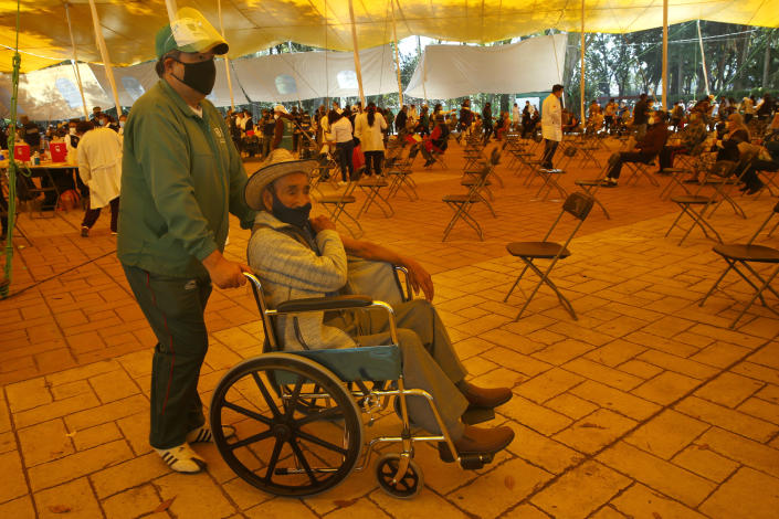 Lucio Bautista, 89, holds onto his right arm as he exits an orange tent in a wheelchair after he was inoculated with a dose of the Russian COVID-19 vaccine Sputnik V, at the Sports Center in the Xochimilco borough of Mexico City, Wednesday, Feb. 24, 2021. (AP Photo/Marco Ugarte)