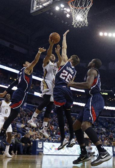 New Orleans Pelicans shooting guard Eric Gordon (10) goes to the basket between Atlanta Hawks power forward Gustavo Ayon (14) and shooting guard Kyle Korver (26) in the first half of an NBA basketball game in New Orleans, Wednesday, Feb. 5, 2014. (AP Photo/Gerald Herbert)