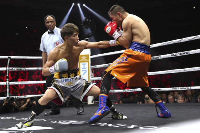 Japan's Naoya Inoue, left, sends a left to Philippines' Nonito Donaire in the first round of their World Boxing Super Series bantamweight final match in Saitama, Japan, Thursday, Nov. 7, 2019. Inoue beat Donaire with a unanimous decision to win the championship. (AP Photo/Toru Takahashi)