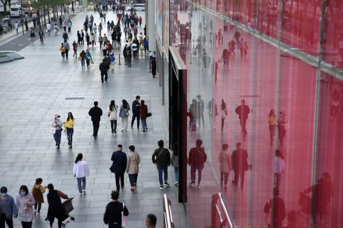 People wearing face masks are seen at a shopping area in Beijing