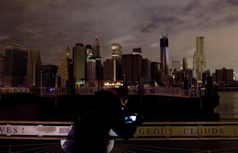 A woman photographs the Manhattan skyline, Tuesday, Oct. 30, 2012 in New York. Much of lower Manhattan is without electric power following the impact of superstorm Sandy. (AP Photo/Mark Lennihan)