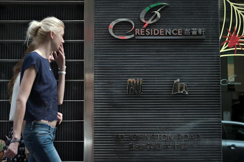 People walk in front of the entrance to the Hong Kong tower block where British banker Rurik Jutting allegedly murdered two women (AFP Photo/Nicolas Asfouri)