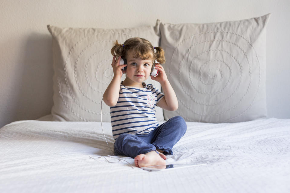 beautiful little girl using tablet and listening to music on headset on bed. Home, indoors. LIfestyle