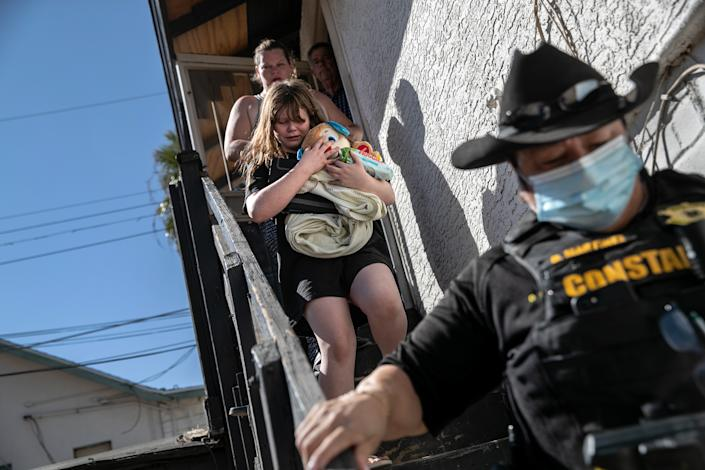 Maricopa County constable Darlene Martinez escorts a family out of their apartment after serving an eviction order for non-payment on September 30, 2020 in Phoenix, Arizona. (John Moore/Getty Images)