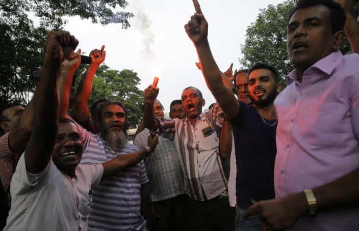 Supporters of ousted Sri Lankan Prime Minister Ranil Wickremesinghe celebrate outside the supreme court complex in Colombo, Sri Lanka, Thursday, Dec. 13, 2018. Sri Lanka's Supreme Court unanimously ruled as unconstitutional President Maithripala Sirisena's order to dissolve Parliament and call for fresh elections, a much-anticipated verdict Thursday that further embroils the Indian Ocean island nation in political crisis.(AP Photo/Eranga Jayawardena)