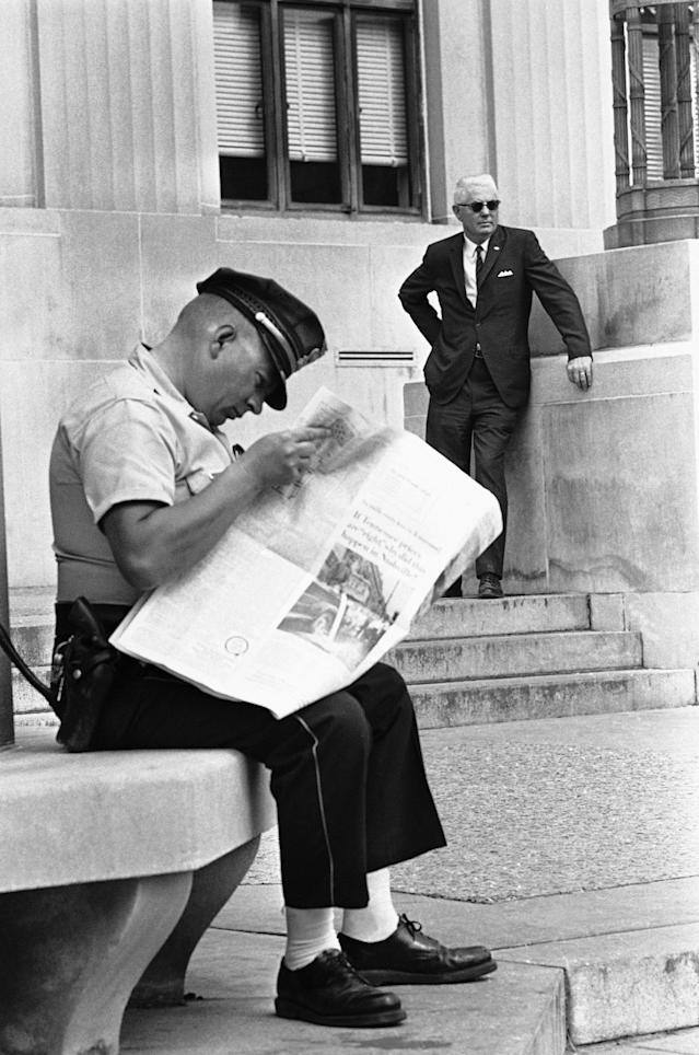 <p>A Meridian, Miss., policemen reads a newspaper containing stories about a trial of 18 white men charged with conspiracy in the slaying of three civil rights workers in 1964 outside the Federal building in Oct. 17, 1967 in Meridian, Miss., as Bernard Akin (background) looks on. Akin is one of 18 white men on trial in the case. (Photo: AP) </p>