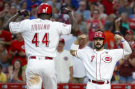 Cincinnati Reds' Aristides Aquino (44) celebrates with Eugenio Suarez (7) after Aquino hit a two-run home run off Chicago Cubs starting pitcher Cole Hamels during the third inning of a baseball game, Thursday, Aug. 8, 2019, in Cincinnati. (AP Photo/John Minchillo)