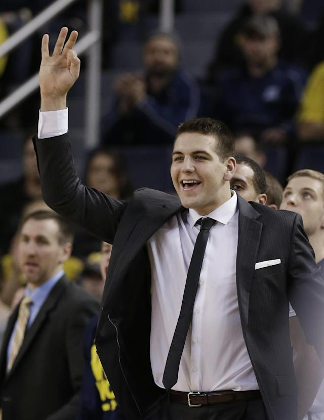 Michigan forward Mitch McGary signals after a 3-point basket by a teammate during the first half of an NCAA college basketball game against Holy Cross in Ann Arbor, Mich., Saturday, Dec. 28, 2013. After weeks of practicing and playing through pain, McGary has decided to have surgery on his lower back, the school announced Friday. He is out indefinitely. (AP Photo/Carlos Osorio)