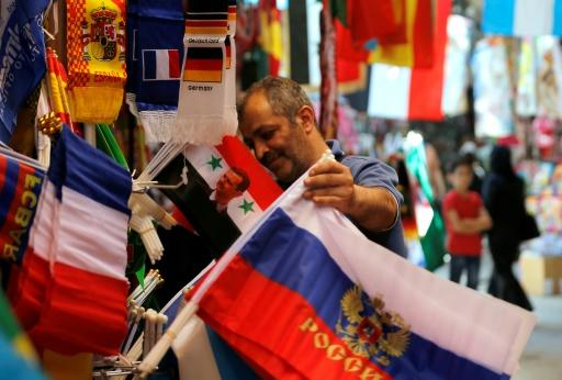 A Syrian vendor holds a Russian flag at a stall at a Damascus street market selling paraphernalia to football fans ahead of the World Cup picture taken on June 7, 2018 shows flags of countries participating in the upcoming 2018 FIFA World Cup on display among other flags outside a vendor's stall to be sold for football supporters and viewers, at a market street in the old city of the Syrian capital Damascus