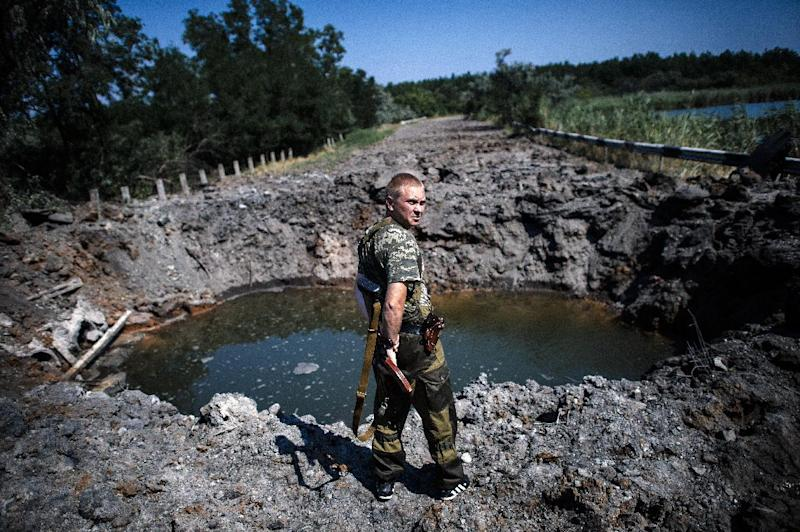 A pro-Russian gunman stands next a bomb crater after shelling near Donetsk on August 14, 2014 (AFP Photo/Dimitar Dilkoff)