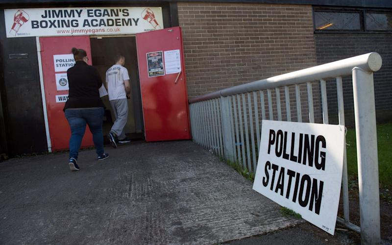 Voters arrive at a polling station in Manchester on Thursday - Credit: Oli Scarff/AFP