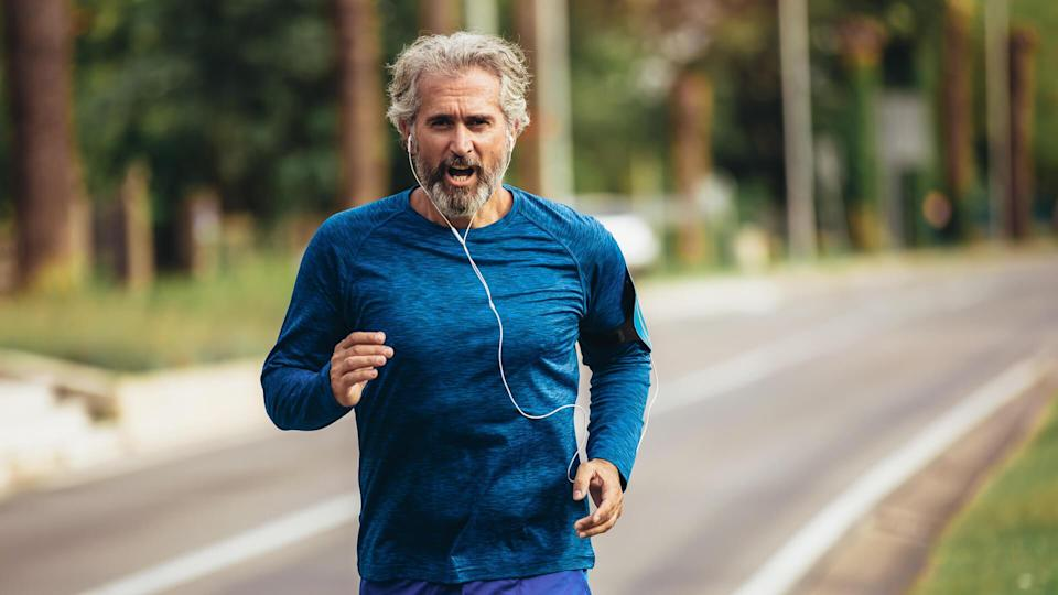 Active senior man jogging on a sunny day.