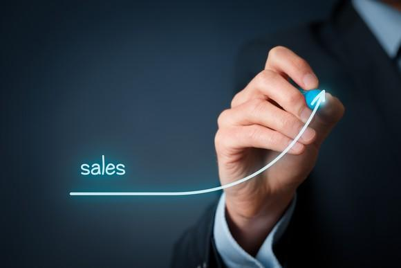 """A person in a suit drawing an upward-trending curve with the word """"sales"""" written above the start of the trend line."""
