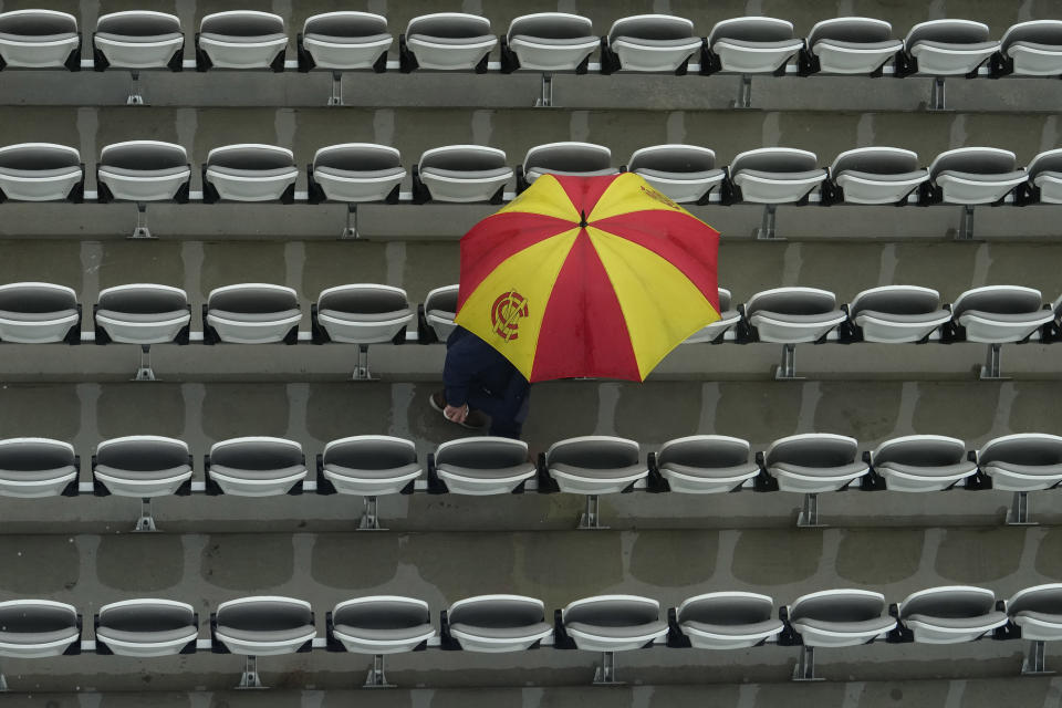 A fan with an umbrella in the colours of the Marylebone Cricket Club (MCC), waits as rain delays the start of play on the third day of the Test match between England and New Zealand at Lord's cricket ground in London, Friday, June 4, 2021. (AP Photo/Kirsty Wigglesworth)