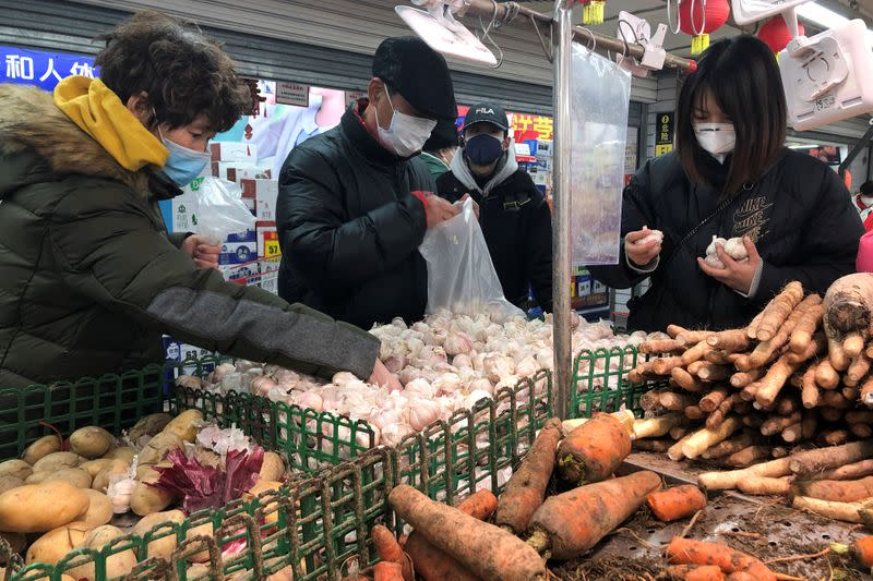 People wearing face masks select vegetables at a supermarket, as the country is hit by an outbreak of the new coronavirus, in Beijing