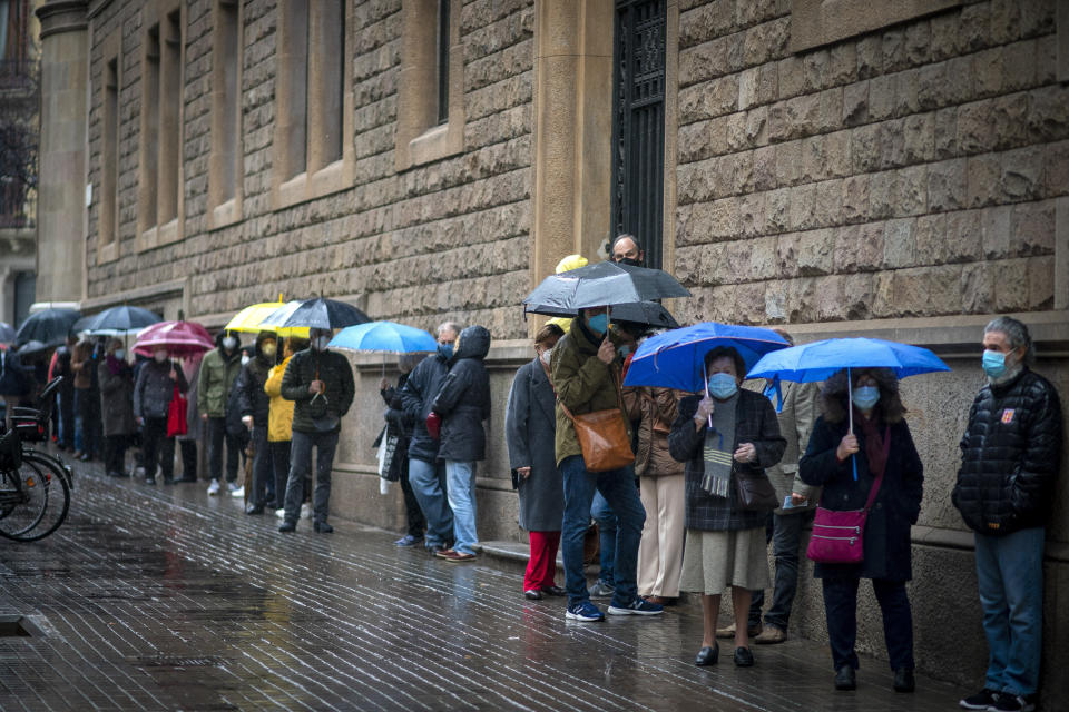 People line up outside a polling station, before casting their vote for the regional Catalan election in Barcelona, Spain, Sunday, Feb. 14, 2021. Over five million voters are called to the polls on Sunday in Spain's northeast Catalonia for an election that will measure the impact of the coronavirus pandemic on the restive region's secessionist movement. (AP Photo/Emilio Morenatti)