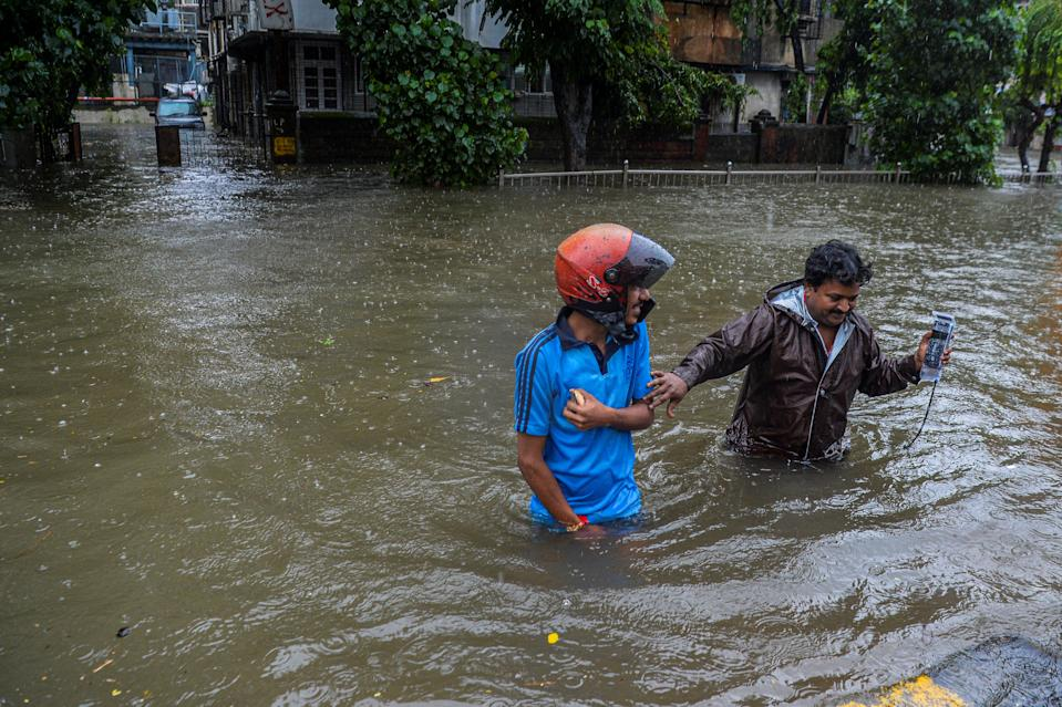 Commuters wade in waist deep water crossing a flooded road during a heavy monsoon rain in Mumbai on August 4, 2020. (Photo by INDRANIL MUKHERJEE/AFP via Getty Images)