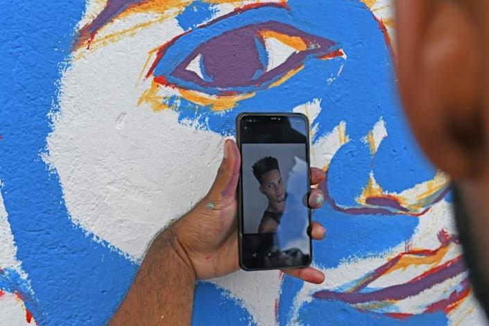 A friend of Cristian Charris looks at a photo on his cell phone as he paints a mural of his dead friend at a basketball court where a tournament was played in his honor (AFP Photo/STR)