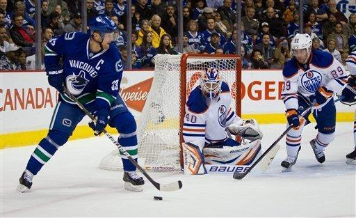 Vancouver Canucks' Henrik Sedin, left, of Sweden, carries the puck from behind the net as Edmonton Oilers goalie Devan Dubnyk, center, and teammate Sam Gagner defend during the first period of an NHL hockey game in Vancouver, British Columbia, on Tuesday, Jan. 24, 2012. (AP Photo/The Canadian Press, Darryl Dyck)