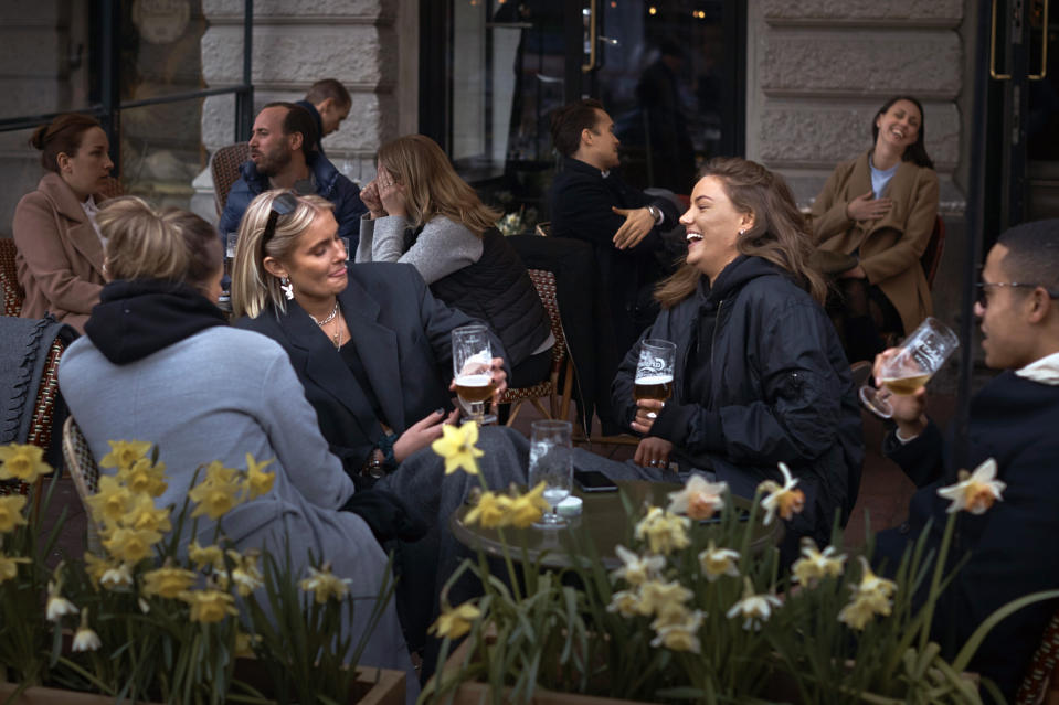 FILE - In this Wednesday, April 8, 2020 file photo people chat and drink outside a bar in Stockholm, Sweden. Sweden's relatively low-key approach to coronavirus lockdowns captured the world's attention when the pandemic first hit Europe. But it also had a per capita death rate much higher than other Nordic countries. Now, as infection numbers surge in much of Europe, Sweden has some of the lowest numbers of new cases and there are only 14 people being treated for the virus in intensive care in the country of 10 million.(AP Photo/Andres Kudacki, File)