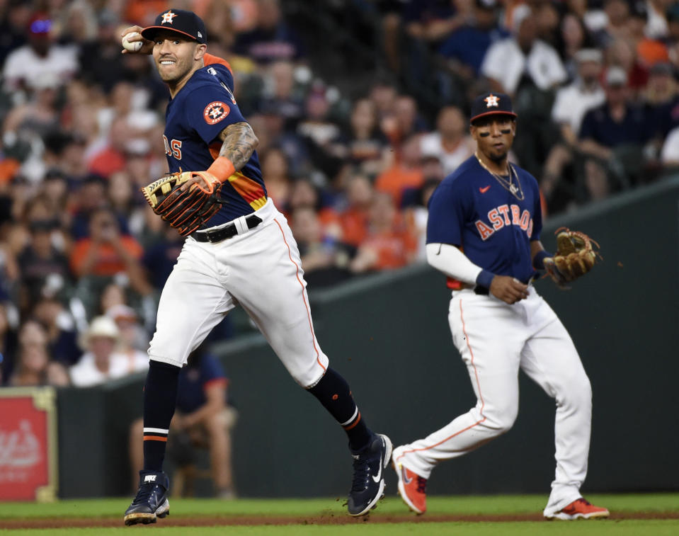 Houston Astros shortstop Carlos Correa, left, throws out Chicago White Sox's Tim Anderson as third baseman Robel Garcia, right, watches during the fifth inning of a baseball game, Saturday, June 19, 2021, in Houston. (AP Photo/Eric Christian Smith)