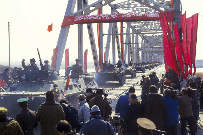 FILE - In this Feb. 15, 1989 file photo, Soviet Army soldiers wave their hands as their unit crosses a bridge on the border between Afghanistan and then Soviet Uzbekistan near the Uzbek town of Termez, Uzbekistan. Afghanistan is marking the 31st anniversary of the Soviet Union's last soldier leaving the country, Saturday, Feb. 15, 2020. This year's anniversary comes as the United States negotiates its own exit after 18 years of war, America's longest. (Leonid Yakutin/Defense Ministry Press Service via AP)