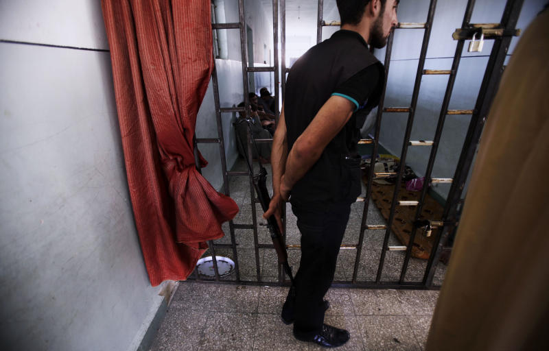 In this Friday, Aug. 24, 2012 photo, a Free Syrian Army Soldier holds his AK-47 while standing by the door of a makeshift prison run by rebels in a former elementary school in Al-Bab on the outskirts of Aleppo, Syria. Many improvised detention centers have sprung up as rebels wrest cities from army control, but these facilities fall under no national or regional authority, causing concern among rights groups. (AP Photo/Muhammed Muheisen)