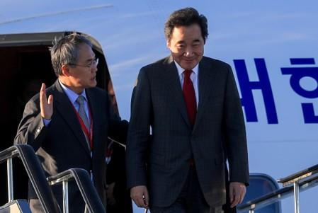 South Korean PM Lee Nak-yon and Ambassador to Russia Woo Yoon-keun disembark from a plane to attend the upcoming Eastern Economic Forum in Vladivostok, on the tarmac at Vladivostok International Airport
