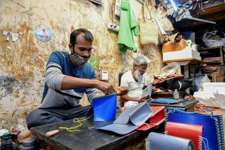 Artisans Rahul Dattatrey Gorey (L) and Kalamudeen Ansari stitch new recycled rubber bags for 'Chamar Studio' by designer Sudheer Rajbhar at a workshop inside Dharavi slum in Mumbai