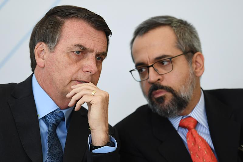 Brazilian President Jair Bolsonaro (L) speaks with his Education Minister Abraham Weintraub during the International Youth Day celebration at Planalto Palace in Brasilia on August 16, 2019. - Bolsonaro criticized a possible victory of Presidential candidate for the Frente de Todos (Front for All) party Alberto Fernandez in the upcoming elections in Argentina. (Photo by EVARISTO SA / AFP) (Photo credit should read EVARISTO SA/AFP via Getty Images)