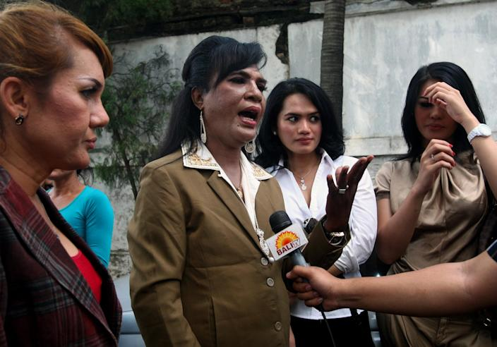 In this Friday, Jan. 20, 2012 photo, an Indonesian transvestite Yulianus Retoblaut who is also known as Mami Yulie, center, is accompanied by fellow transvestites as she is interviewed by a local TV after submitting her name as a candidate for the membership of Indonesian National Commission on Human Rights in Jakarta, Indonesia. Indonesia's attitude toward transgenders is complex. Nobody knows how many of them live in the sprawling archipelagic nation of 240 million, but activists estimate 7 million. However, societal disdain still runs deep - when transgenders act in TV comedies, they are invariably the brunt of the joke. (AP Photo/Dita Alangkara)