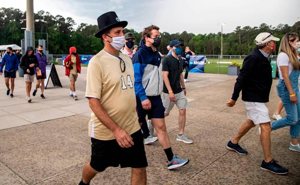 Fans attending the Wake Forest UNC-Chapel Hill's game head to their cars durning a lightning delay during the Division I Men's Soccer Championship quarterfinals at WakeMed Soccer Park in Cary Monday, May 10, 2021.