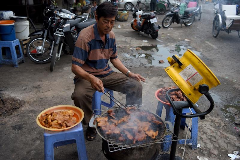 A man grills pork for sale at a market in Phnom Penh, Cambodia, which has banned the import of all pigs and pork products (AFP Photo/TANG CHHIN Sothy)