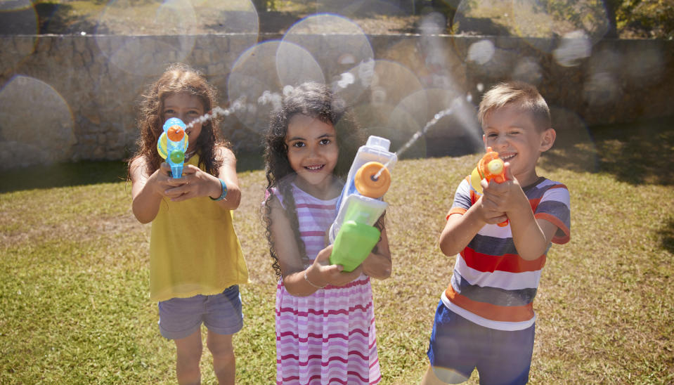 Group of multi-ethnic children aiming water gun to camera on garden in the summer
