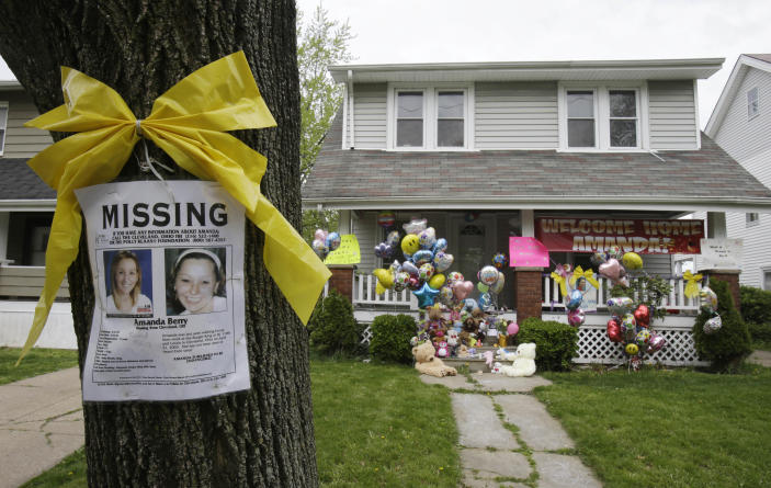 FILE - In this Wednesday, May 8, 2013 file photo, a missing poster still rests on a tree outside the home of Amanda Berry, in Cleveland. For Berry, Gina DeJesus and Michelle Knight, who were freed from captivity inside a Cleveland house earlier this week, the ordeal is not over. Next comes recovery _ from sexual abuse and their sudden, jarring reentry into a world much different than the one they were snatched from a decade ago. (AP Photo/Tony Dejak, File)